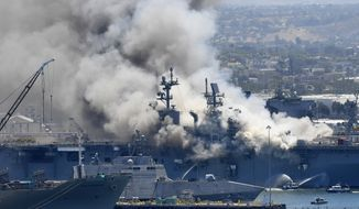 In this July 12, 2020, file photo, smoke rises from the USS Bonhomme Richard in San Diego after an explosion and fire on board the ship at Naval Base San Diego. The U.S. Navy said Thursday, July 29, 2021, that charges have been filed against a sailor who is accused of starting a fire last year that destroyed a warship docked off San Diego. The amphibious assault ship called the USS Bonhomme Richard burned for more than four days and was the Navy's worst U.S. warship fire outside of combat in recent memory. (AP Photo/Denis Poroy, File)