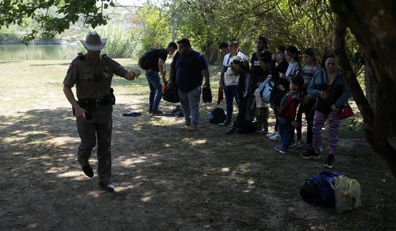 In this June 16, 2021 file photo, Texas Department of Public Safety officers work with a group of migrants who crossed the border and turned themselves in Del Rio, Texas. (AP Photo/Eric Gay, File)  **FILE**