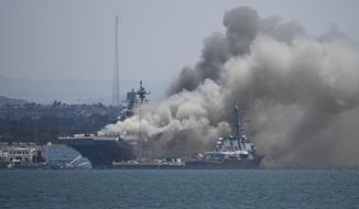 In this July 12, 2020, file photo, smoke rises from the USS Bonhomme Richard at Naval Base San Diego in San Diego after an explosion and fire. The U.S. Navy said Thursday, July 29, 2021, that charges have been filed against a sailor who is accused of starting a fire last year that destroyed a warship docked off San Diego. The amphibious assault ship called the USS Bonhomme Richard burned for more than four days and was the Navy's worst U.S. warship fire outside of combat in recent memory. (AP Photo/Denis Poroy, File)  **FILE**