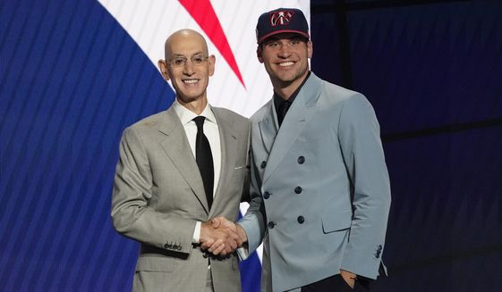 Corey Kispert, right, poses for a photo with NBA Commissioner Adam Silver after being selected 15th overall by the Washington Wizards during the NBA basketball draft, Thursday, July 29, 2021, in New York. (AP Photo/Corey Sipkin)