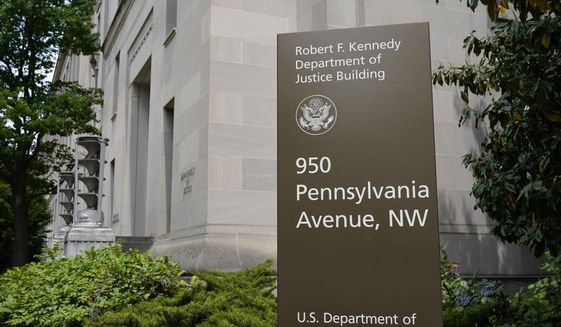 This May 4, 2021, file photo shows a sign outside the Robert F. Kennedy Department of Justice building in Washington. The Russian hackers behind the massive SolarWinds cyberespionage campaign broke into the email accounts some of the most prominent federal prosecutors' offices around the country last year, the Department of Justice said Friday, July 30, 2021. (AP Photo/Patrick Semansky, File)