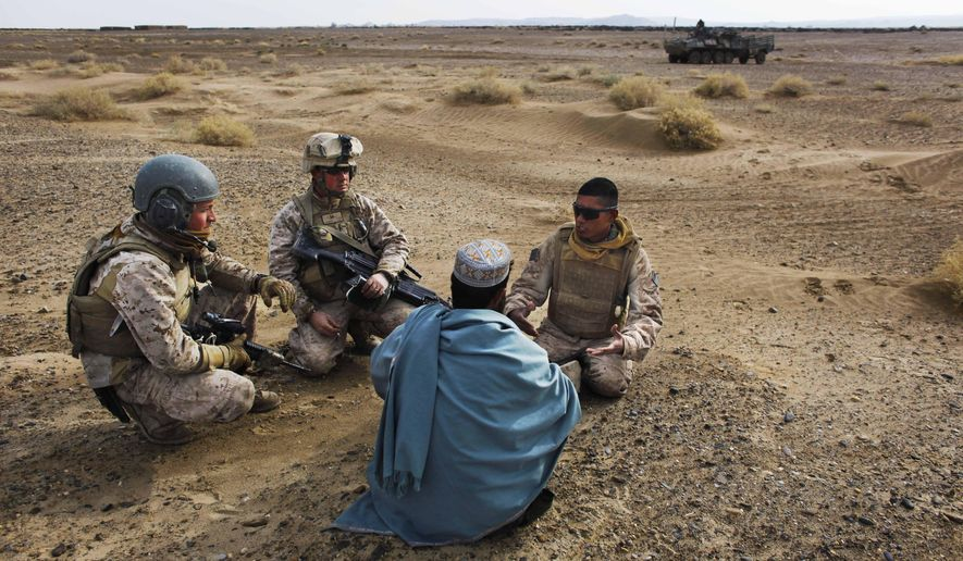 In this Friday, Dec. 11, 2009, file photo, U.S. Marine Sgt. Isaac Tate, left, and Cpl. Aleksander Aleksandrov, center, interview a local Afghan man with the help of a translator from the 2nd MEB, 4th Light Armored Reconnaissance Battalion on a patrol in the volatile Helmand province of southern Afghanistan. More than 200 Afghans were due to land Friday in the United States in the first of several planned evacuation flights for former translators and others as the U.S. ends its nearly 20-year war in Afghanistan. (AP Photo/Kevin Frayer, File)