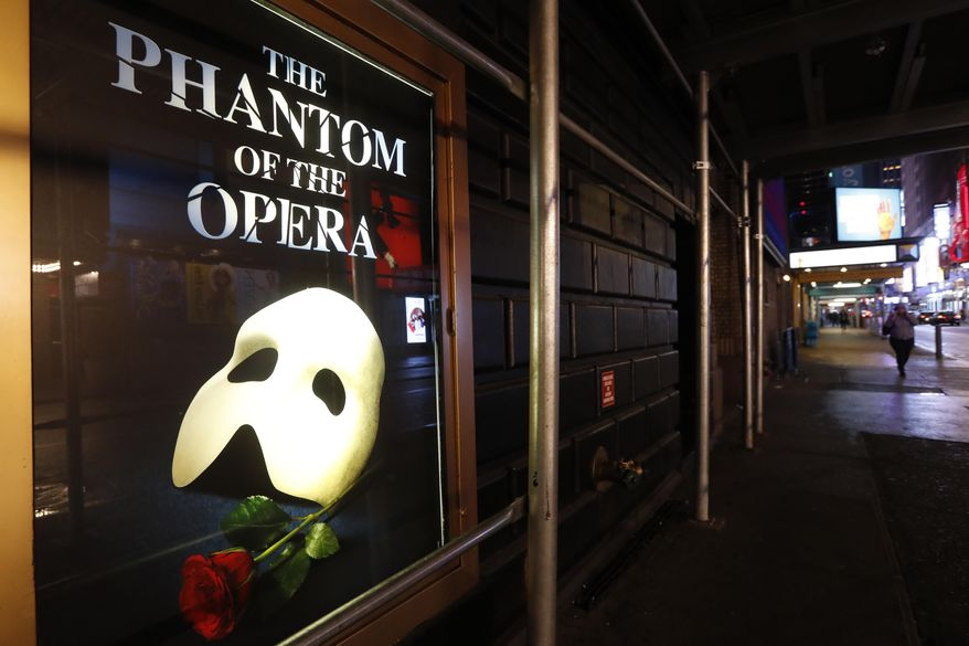 """In this March 12, 2020, file photo, a poster advertising """"The Phantom of the Opera"""" is displayed on the shuttered Majestic Theatre in New York. Broadway theatergoers will need to prove they've been vaccinated for COVID-19 and masks will be required when theaters reopen in the coming weeks, producers announced Friday, July 31, 2021. (AP Photo/Kathy Willens)  **FILE**"""