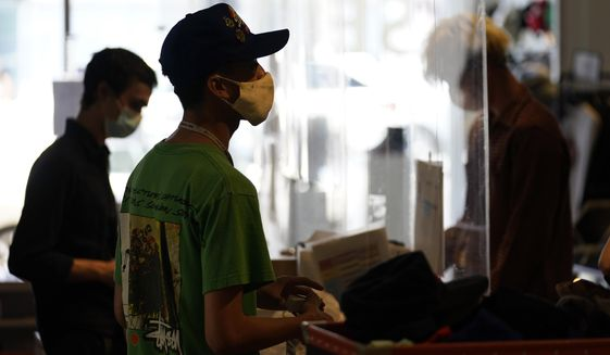 In this July 19, 2021, photo, employees check out customers at 2nd Street second hand store in the Fairfax district of Los Angeles.  New evidence showing the delta variant is as contagious as chickenpox has prompted U.S. health officials to consider changing advice on how the nation fights the coronavirus. Recommending masks for everyone and requiring vaccines for doctors and other health care providers are among measures the Centers for Disease Control and Prevention is considering, Friday, July 30. (AP Photo/Marcio Jose Sanchez) **FILE**