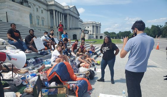 Rep. Cori Bush, Missouri Democrat, is seen at right in black, with a group of progressive protesters on the steps of the U.S. Capitol. Ms. Bush is protesting her House colleagues going on August recess as the federal eviction moratorium expires. She is urging House leadership to return to the Hill to pass an extension on the moratorium. (Photo by Kery Murakami/The Washington Times)