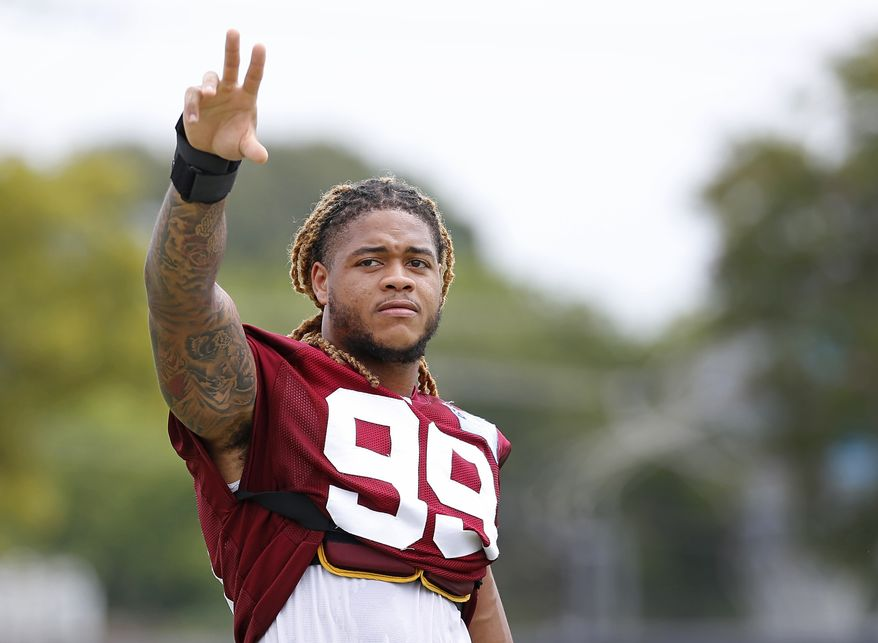Chase Young (99) waves to the crowd at the Washington Football Team's NFL training camp Saturday, July 31, 2021, in Richmond, Va. (AP Photo/Dean Hoffmeyer)