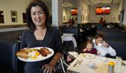 Jeannie Kim holds her popular bacon and eggs breakfast at her restaurant in San Francisco on Friday, July 30, 2021. Thanks to a reworked menu and long hours, Jeannie Kim managed to keep her San Francisco restaurant alive during the coronavirus pandemic. That makes it all the more frustrating that she fears her breakfast-focused diner could be ruined within months by new rules that could make one of her top menu items — bacon — hard to get in California. (AP Photo/Eric Risberg)