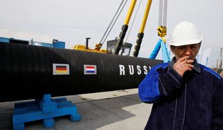 In this Friday, April 9, 2010, file photo, a Russian construction worker smokes in Portovaya Bay some 170 kms (106 miles) northwest from St. Petersburg, Russia, during a ceremony marking the start of Nord Stream pipeline construction. (AP Photo/Dmitry Lovetsky, File)