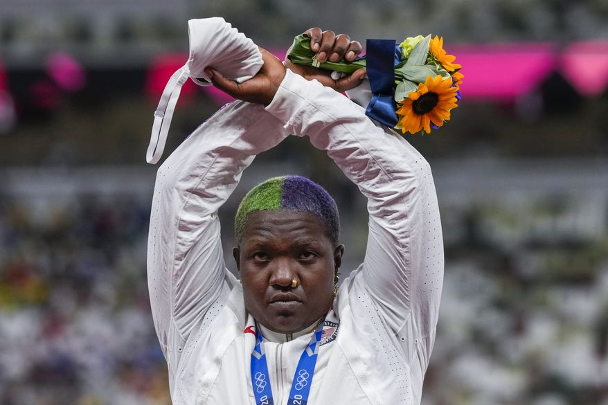 Raven Saunders, of the United States, poses with her silver medal on women's shot put at the 2020 Summer Olympics, Sunday, Aug. 1, 2021, in Tokyo, Japan. During the photo-op at her medals ceremony Sunday night, Saunders stepped off the podium, lifted her arms above her head and formed an X with her wrists. (AP Photo/Francisco Seco)
