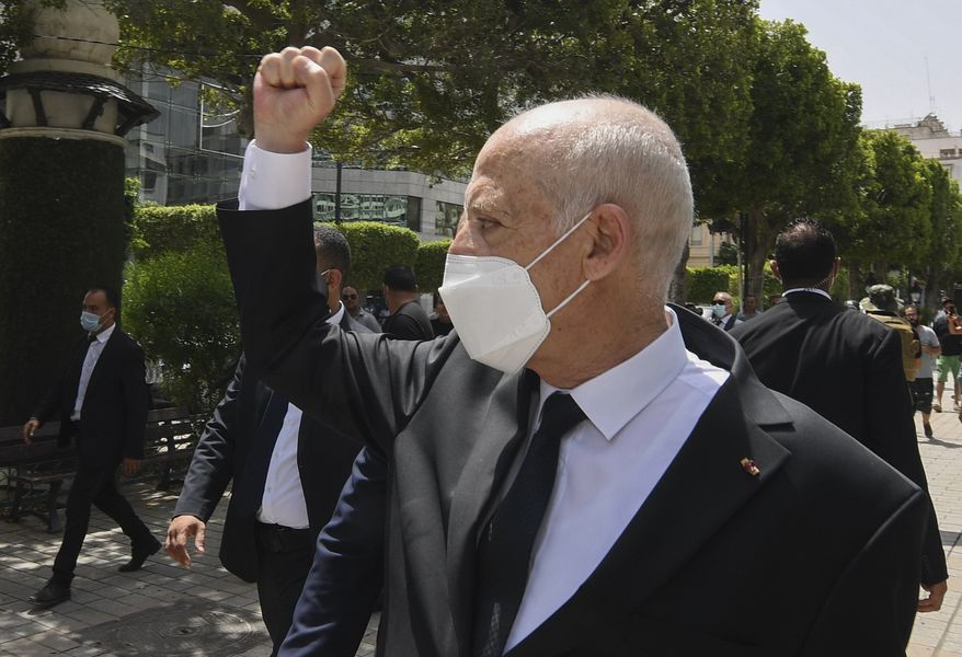 Tunisian President Kais Saied raises his fist to bystanders as he stroll along the avenue Bourguiba in Tunis, Tunisia, Sunday, Aug. 1, 2021. President Kais Saied claimed on Sunday that some desperate youth are being paid to try to leave Tunisia illegally for Europe, saying the goal is to damage the country from within. (Slim Abid/Tunisian Presidency via AP)