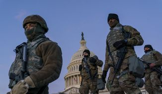 In this Jan. 19, 2021, photo, National Guard troops reinforce the security zone on Capitol Hill in Washington. Over the past year, National Guard members have been called in to battle the COVID-19 pandemic, natural disasters and race riots. (AP Photo/J. Scott Applewhite) **FILE**