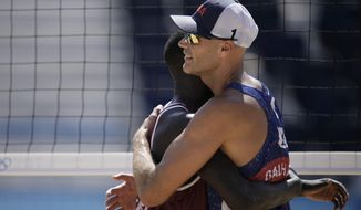 Cherif Younousse, left, of Qatar, hugs Philip Dalhausser, of the United States, after Qatar won a men's beach volleyball match at the 2020 Summer Olympics, Sunday, Aug. 1, 2021, in Tokyo, Japan. (AP Photo/Felipe Dana)