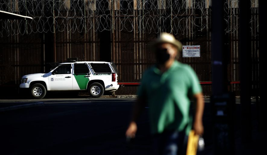 A Border Patrol vehicle sits near the border wall separating Mexicali, Mexico from Calexico, Calif., in Calexico. (AP Photo/Gregory Bull) **FILE**
