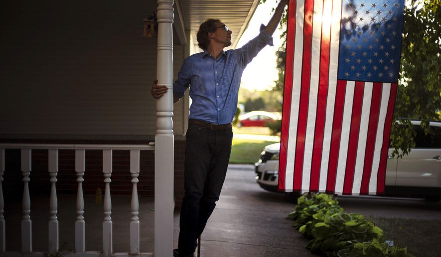 In this Aug. 18, 2020, file photo, Outagamie County Executive Tom Nelson adjusts the American flag hanging off his front porch in Appleton, Wis. AP Photo/David Goldman, File)