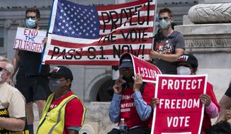 Voting rights activists hold signs and banners during a demonstration supporting voting rights during a rally on Capitol Hill, in Washington, Monday, Aug. 2, 2021. (AP Photo/Jose Luis Magana)