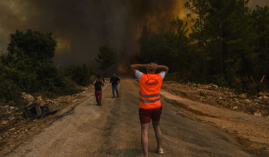 People run away from the fire-devastated Sirtkoy village, near Manavgat, Antalya, Turkey, Sunday, Aug. 1, 2021. More than 100 wildfires have been brought under control in Turkey, according to officials. The forestry minister tweeted that five fires are continuing in the tourist destinations of Antalya and Mugla. (AP Photo)