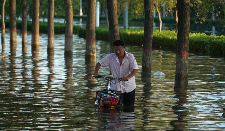 In this July 26, 2021, file photo, a man pushes a scooter through floodwaters in Xinxiang in central China's Henan Province. Chinese authorities have announced a huge jump in the death toll from recent floods. The Henan province government said Monday, Aug. 2, 2021, that over 300 have people died and at least 50 remain missing. (AP Photo/Dake Kang, File)