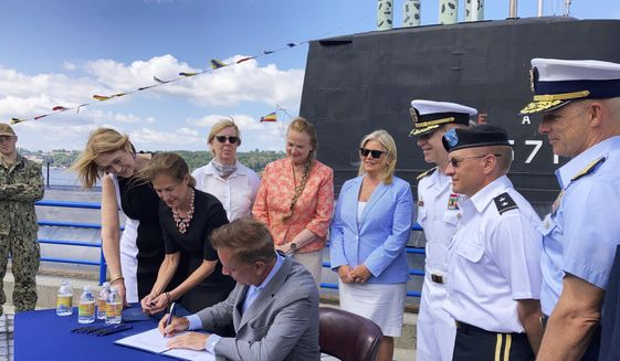 Connecticut Gov. Ned Lamont signs copies of a bill concerning military spouses. Monday, Aug. 2, 2021, at the Submarine Force Museum in Groton, Conn. The law, which takes effect Oct. 1, makes it easier for spouses of active duty military personnel to obtain state occupational licenses. Some have had to wait months, if not years, to get their license from another state recognized by Connecticut. Standing next to Lamont at the table is Lt. Gov. Susan Bysiewicz. Also attending are state legislators from southeastern Connecticut, and military officers assigned to the U.S. Submarine Base, New London, including Capt. Todd Moore, third from right, commanding officer at the base. (AP Photo/Susan Haigh)