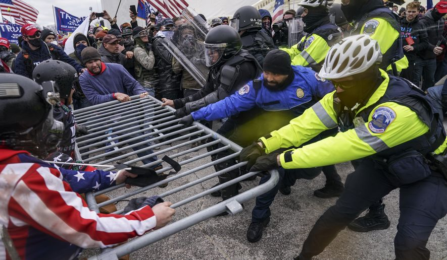 FILE - In this Jan. 6, 2021, file photo violent insurrectionists loyal to President Donald Trump hold on to a police barrier at the Capitol in Washington.  The Senate has voted to award Medals of Honor to the Capitol Police and the Metropolitan Police Department for protecting Congress during the Jan. 6 insurrection, sending the legislation to President Joe Biden for his signature. The bill passed by voice vote with no objections. The four medals will be displayed at Capitol Police headquarters, the Metropolitan Police Department, the U.S. Capitol and the Smithsonian Institution. Hundreds of officers from the two police departments responded to the attack as the mob of former President Donald Trumps supporters broke into the building and interrupted the certification of Biden's victory. (AP Photo/John Minchillo, File)