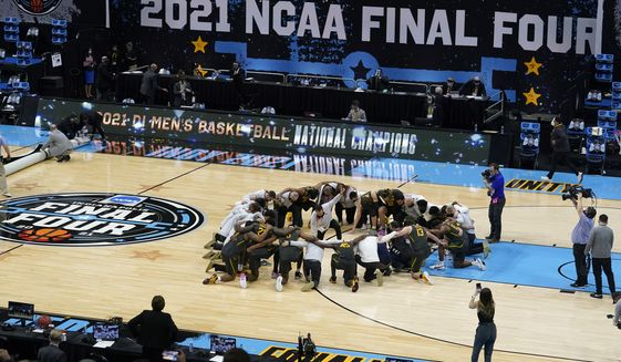 Baylor players huddle on the court at the end of the championship game against Gonzaga in the men's Final Four NCAA college basketball tournament in Indianapolis, in this Monday, April 5, 2021, file photo. A law firm hired to investigate gender equity concerns at NCAA championship events released a blistering report Tuesday, Aug. 3, 2021, that recommended holding the men's and women's Final Fours at the same site and offering financial incentives to schools to improve their women's basketball programs.  (AP Photo/Darron Cummings, File) **FILE**
