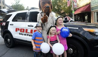 Posing for a photo with McGruff the Crime Dog are, from left, Damien Foss, Mia Foss and Sophia Foss, all of Pottsville, Pa., during Pottsville Night Out on North Centre Street in downtown Pottsville, Pa., on Tuesday evening, Aug. 3, 2021. The event coincides with National Night Out. (Jacqueline Dormer/Republican-Herald via AP)