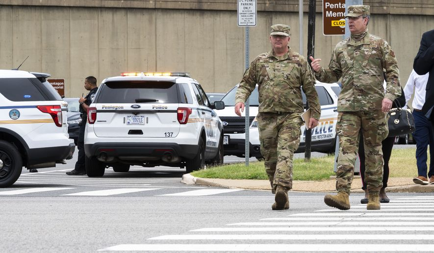 Members of the Air Force walk away from the Pentagon, Tuesday, Aug. 3, 2021, in Washington. Gunshots were fired Tuesday morning near the entrance of the Pentagon, resulting in multiple injuries. The facility, the headquarters of the U.S. military, was temporarily placed on lockdown. The Arlington County Fire Department reported multiple patients, but it wasn't immediately clear if they had been shot and the extent of their injuries were unknown. (AP Photo/Cliff Owen)