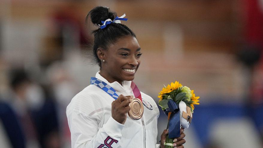 U.S. gymnast Simone Biles poses with her bronze medal for the artistic gymnastics women's balance beam apparatus at the 2020 Summer Olympics, Tuesday, Aug. 3, 2021, in Tokyo, Japan. (AP Photo/Natacha Pisarenko) ** FILE **