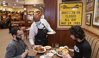 In this Sept. 30, 2020, file photo, Waiter Lenworth Thompson serves lunch to David Zennario, left, and Alex Ecklin at Junior's Restaurant in New York. New York City will soon require proof of COVID-19 vaccinations for anyone who wants to dine indoors at a restaurant, see a performance or go to the gym, Mayor Bill de Blasio announced Tuesday, Aug. 3, making it the first big city in the U.S. to impose such restrictions. (AP Photo/Mark Lennihan, File)