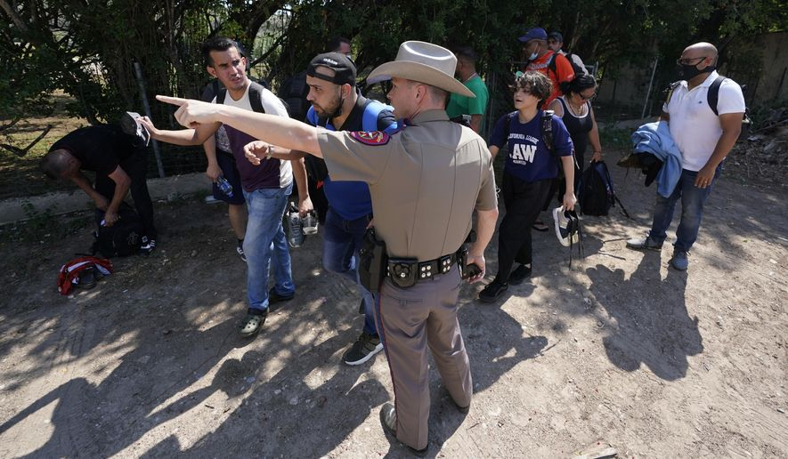 In this Wednesday, June 16, 2021, photo, a Texas Department of Public Safety officer in Del Rio, Texas, directs a group of migrants who crossed the border and turned themselves in. The Biden administration sued Texas on Friday, July 30, 2021, to prevent state troopers from stopping vehicles carrying migrants on grounds that they may spread COVID-19, warning that the practice would exacerbate problems amid high levels of crossings on the state's border with Mexico. (AP Photo/Eric Gay) **FILE**