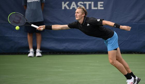 Sebastian Korda reaches for a shot against Vasek Pospisil, of Canada, during a match in the Citi Open tennis tournament, Tuesday, Aug. 3, 2021, in Washington. (AP Photo/Nick Wass)