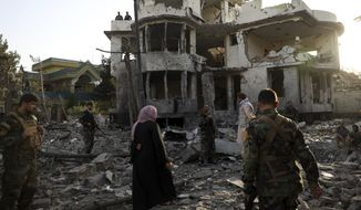 Afghan security personnel inspect a damaged building in the aftermath of an attack in Kabul, Afghanistan, Wednesday, Aug. 4, 2021. A powerful explosion rocked an upscale neighborhood of Afghanistan's capital Tuesday in an attack that apparently targeted the country's acting defense minister. (AP Photo/Rahmat Gul)