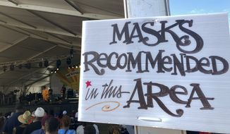 In this July 31, 2021 photo, a sign recommends attendees of the Newport Jazz Festival wear masks in a tented area where singer Ledisi performs in Newport, R.I. Festival-goers were also required to digitally upload proof of COVID-19 vaccination or a recent negative test. (Matt OBrien/AP Photo)