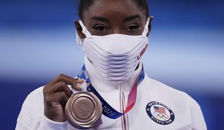 Simone Biles, of the United States, poses with her bronze medal after balance beam competition during the artistic gymnastics women's apparatus final at the 2020 Summer Olympics, Tuesday, Aug. 3, 2021, in Tokyo, Japan. (AP Photo/Ashley Landis)