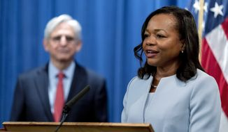 Assistant Attorney General for Civil Rights Kristen Clarke, right, accompanied by Attorney General Merrick Garland, left, speaks at a news conference at the Department of Justice in Washington, Thursday, Aug. 5, 2021, to announce that the Department of Justice is opening an investigation into the city of Phoenix and the Phoenix Police Department. (AP Photo/Andrew Harnik) **FILE**