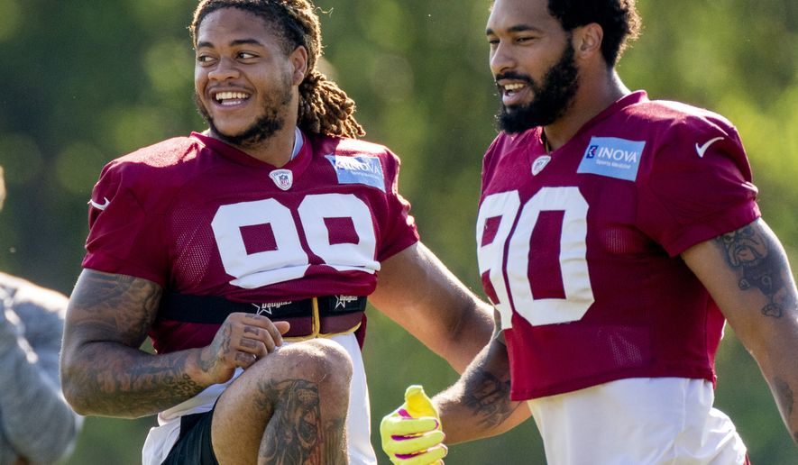 Washington Football Team defensive end Chase Young (99) and Washington Football Team linebacker Montez Sweat (90) at the team's NFL football training camp practice in Ashburn, Va., Thursday, Aug. 5, 2021. (AP Photo/Andrew Harnik)