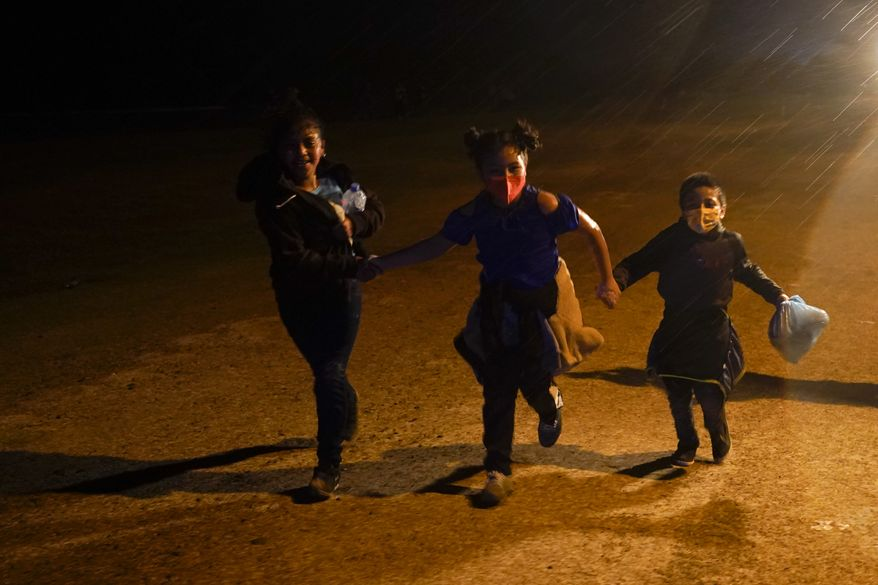 In this May 11, 2021, photo, three young migrants hold hands as they run in the rain at an intake area after turning themselves in upon crossing the U.S.-Mexico border in Roma, Texas. An official says the Biden administration has begun flying some Central American families deep into Mexico as authorities encounter more families and unaccompanied children at the U.S.-Mexico border. (AP Photo/Gregory Bull) **FILE**