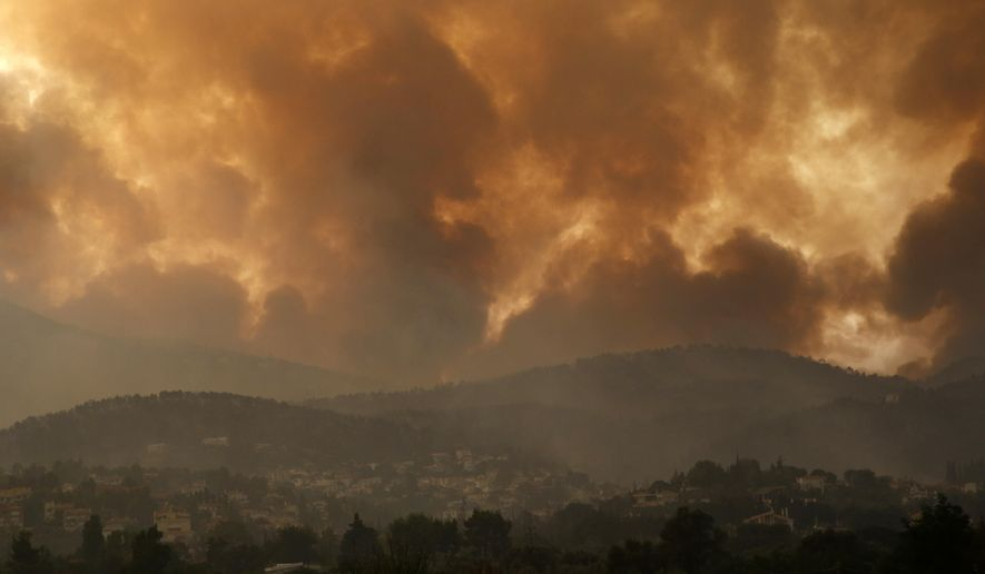 Smoke spreads over Parnitha mountain during a wildfire in Ippokratios Politia village, about 35 kilometres (21 miles), northern Athens, Greece, Friday, Aug. 6, 2021. Thousands of people fled wildfires burning out of control in Greece and Turkey on Friday, including a major blaze just north of the Greek capital of Athens that claimed one life, as a protracted heat wave left forests tinder-dry and flames threatened populated areas and electricity installations. (AP Photo/Lefteris Pitarakis)
