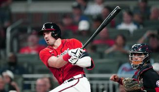Atlanta Braves' Adam Duvall, left, drives in a run with a double as Washington Nationals catcher Tres Barrera looks on in the fifth inning of a baseball game Friday, Aug. 6, 2021, in Atlanta. (AP Photo/John Bazemore)