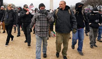 In this Jan. 6, 2021, file photo, Proud Boys including Joseph Biggs, front left, walks toward the U.S. Capitol in Washington, in support of President Donald Trump. With the megaphone is Ethan Nordean, second from left. Outside pressures and internal strife are roiling two far-right extremist groups after members were charged in the attack on the U.S. Capitol. Former President Donald Trump's lies about a stolen 2020 election united an array of right-wing supporters, conspiracy theorists and militants on Jan. 6. (AP Photo/Carolyn Kaster, File)