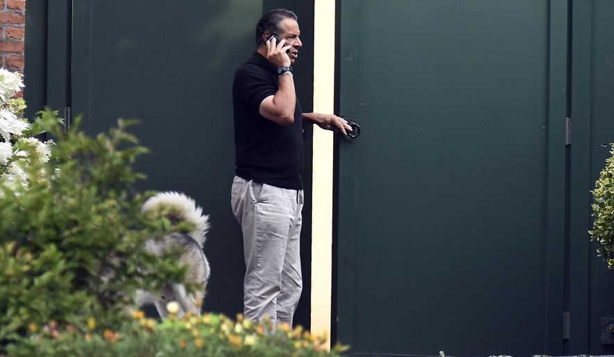 El gobernador Andrew Cuomo habla por teléfono mientras camina con su perro Captain en la Mansión Ejecutiva del estado de Nueva York, el sábado 7 de agosto de 2021, en Albany, NY Una investigación encontró que Cuomo acosó sexualmente a varias mujeres dentro y fuera del gobierno estatal.  (Foto AP / Hans Pennink)