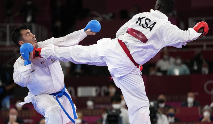 Sajad Ganjzadeh of Iran, left, is injured while competing against Tareg Hamedi of Saudi Arabia in their men's kumite +75kg gold medal bout for karate at the 2020 Summer Olympics, Saturday, Aug. 7, 2021, in Tokyo, Japan. (AP Photo/Vincent Thian)