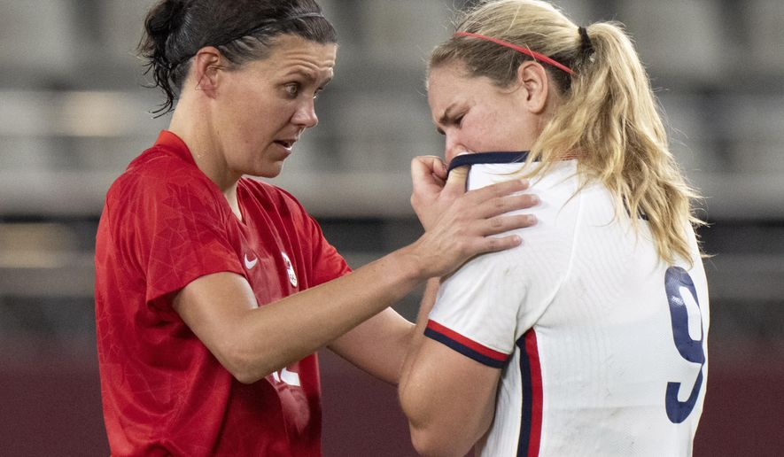 Team Canada forward Christine Sinclair, left, consoles Team United States midfielder Lindsey Horan (9) after their semifinal soccer match at the Tokyo Olympics in Kashima, Japan, Monday, Aug. 2, 2020. Canada won 1-0. (Frank Gunn/The Canadian Press via AP)