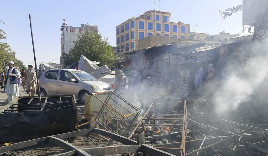 Smoke rises from damaged shops after fighting between Taliban and Afghan security forces in Kunduz city, northern Afghanistan, Sunday, Aug. 8, 2021. Taliban fighters Sunday took control of much of the capital of  Kunduz province, including the governor's office and police headquarters, a provincial council member said. (AP Photo/Abdullah Sahil)