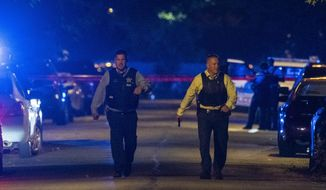 Chicago police work the scene where two police officers where shot during a traffic stop in the 6300 block of South Bell in the West Englewood neighborhood, Saturday, Aug. 7, 2021. (Tyler LaRiviere/Chicago Sun-Times via AP)