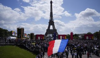 A man unfurls a French flag at the Olympics fan zone at Trocadero Gardens in front of the Eiffel Tower in Paris, Sunday, Aug. 8, 2021. A giant flag will be unfurled on the Eiffel Tower in Paris Sunday as part of the handover ceremony of Tokyo 2020 to Paris 2024, as Paris will be the next Summer Games host in 2024. The passing of the hosting baton will be split between the Olympic Stadium in Tokyo and a public party and concert in Paris. (AP Photo/Francois Mori) **FILE**