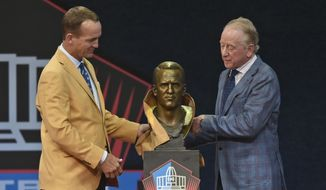 Peyton Manning, left, a member of the Pro Football Hall of Fame Class of 2021, and his presenter and father Archie Manning unveil a bust of Peyton during the induction ceremony at the Pro Football Hall of Fame, Sunday, Aug. 8, 2021, in Canton, Ohio. (AP Photo/David Richard)