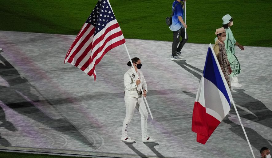 Kara Winger, of the United States of America, and Steven Da Costa, of France, carry their country's flags during the closing ceremony in the Olympic Stadium at the 2020 Summer Olympics, Sunday, Aug. 8, 2021, in Tokyo, Japan. (AP Photo/Vincent Thian)