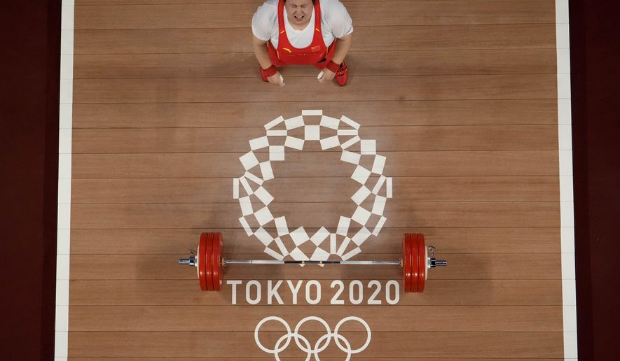 Li Wenwen of China shouts in celebration after setting a new Olympic record in the women's +87kg weightlifting event at the 2020 Summer Olympics, Monday, Aug. 2, 2021, in Tokyo, Japan. (AP Photo/Luca Bruno)