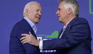 In this July 23, 2021, file photo, President Joe Biden greets Virginia Democratic gubernatorial candidate Terry McAuliffe as he arrives to speak at a campaign event for McAuliffe at Lubber Run Park, in Arlington, Va. (AP Photo/Andrew Harnik, File)
