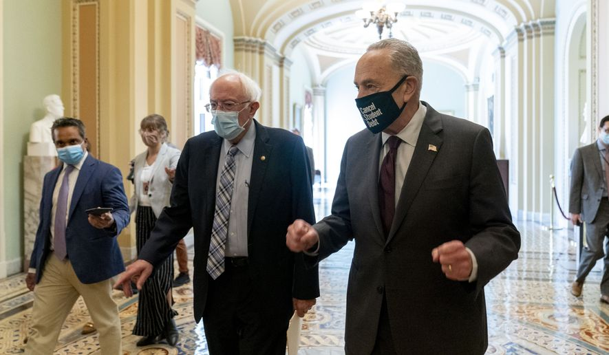 Sen. Bernie Sanders, I-Vt., left, and Senate Majority Leader Chuck Schumer of N.Y., right, speak to members of the media as they walk out of a budget resolution meeting at the Capitol in Washington, Monday, Aug. 9, 2021. (AP Photo/Andrew Harnik)
